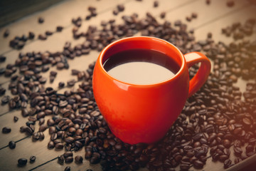 photo of beautiful cup of coffee near roasted beans on the wonderful brown wooden background