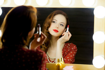 portrait of beautiful young woman holding lipstick and looking at herself in the mirror