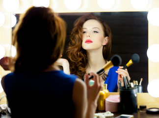 portrait of beautiful young woman holding brush and looking at herself in the mirror