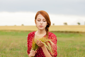 portrait of beautiful young woman with branch of wheat on the wonderful field background