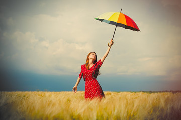 portrait of beautiful young woman with umbrella on the wonderful wheat field background