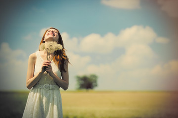 portrait of beautiful young woman with bunch of dandelions on the wonderful field background