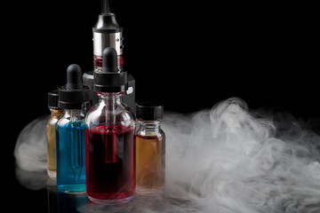 Electronic cigarette and e-liquids on black background with smoke