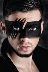 fantasy art makeup. man with black painted mask on face. Close up Portrait. Professional Fashion Makeup.