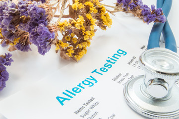 Printed result of allergy test (blood or skin) lies next to flowers with falling pollen and stethoscope. Concept photo for analysis of presence allergies to food, pollen, hair or wools in human