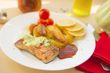 Fried salmon and vegetables on wooden table