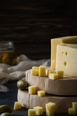 Swedish hard yellow cheese with holes chopped on wooden slices with green olives on dark rustic background