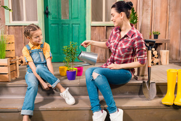 Side view of smiling mother and daughter sitting on porch and watering plant