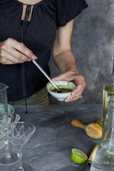 A women is preparing a matcha wine cocktail. Photographed from front view on a grey background.