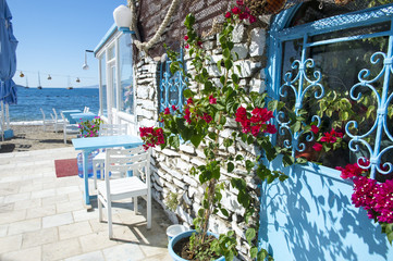 Scenic view of Turkish alley with bougainvillea flowers growing along a wall in classic Mediterranean colors leading to the beach