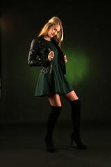 Fotomodel posiert in Lederjacke und Kleid in grün