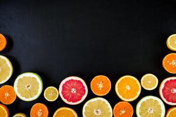 Citrus fruits, vitamin mix on dark background. Flat lay, top view. Tropical summer mix grapefruit, orange, mandarin, lime