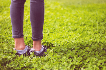 Young girl feet in sport shoes sneakers on green grass on meadow