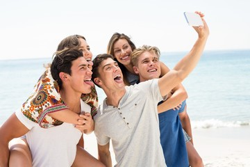 Friends taking selfie at beach on sunny day