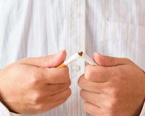 Man trying to quit smoking by breaking a cigarette. Conceptual image. Close-up