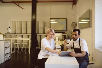 Male and female barista having coffee while using digital tablet
