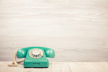 Retro mint green telephone on wooden table