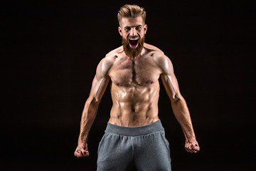 shirtless bearded bodybuilder posing and yelling isolated on black in studio