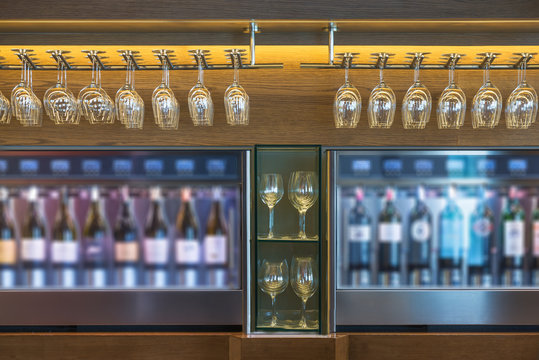 Empty glasses for wine above a bar rack with wine cooler in restaurant
