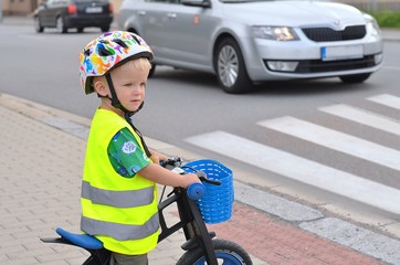 Little boy standing at a pedestrian crossing and looking around. Child must be careful. There is traffic.