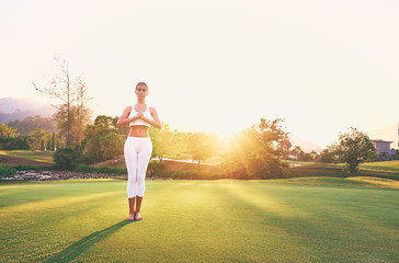 Yoga at park with view of the mountains, with sunlight. Young woman in asana pose standing on green grass. Concept of calm and meditation.