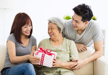 happy  young couple giving  present to grandmother