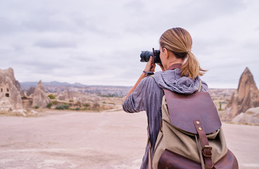 Traveling and photography. Young woman with camera and backpack taking picture at Cappadocia, Turkey.
