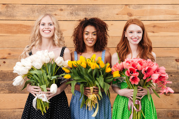 Three smiling women showing bouquets of flowers at camera