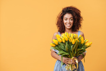 Pretty African woman holding bouquet of flowers
