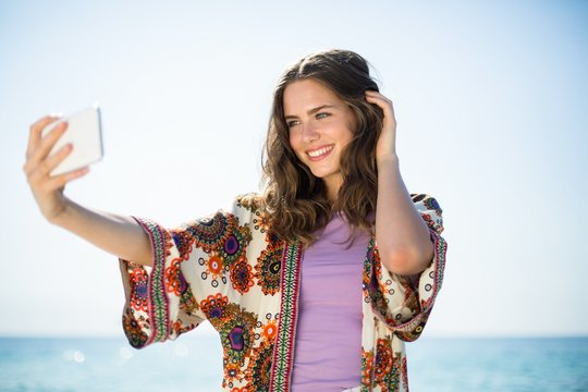 Woman smiling while taking selfie against sky