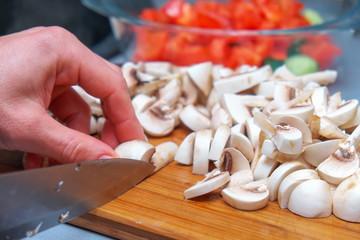 Сhef cutting mushrooms on wooden cutting board, prepares a salad