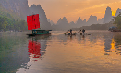 Fisherman sits on traditional bamboo boats at sunrise (boat with a red sail in the background) - Li River, Xingping, China