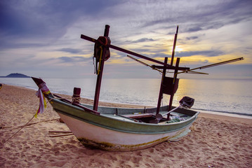 Fishing boats on the beach over cloudy sky in the morning at Prachuap Khiri Khan, Thailand.