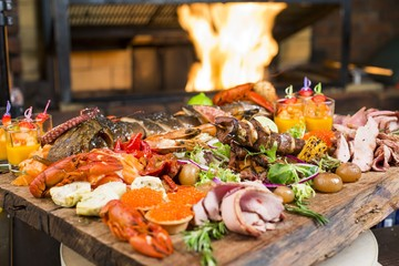 Fresh seafood and meat platter on wooden table