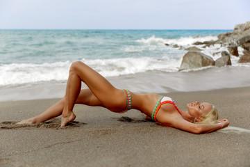 Bikini model girl posing sexy at tropical beach location. Vogue style
