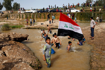 """A boy holds the Iraqi flag as he plays in the water with other children during a Friday holiday at Shallalat district (Arabic for """"waterfalls"""") in eastern Mosul"""