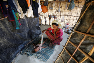 Rohingya mother fans her sleeping child during noon at Balukhali Makeshift Refugee Camp in Cox's Bazar