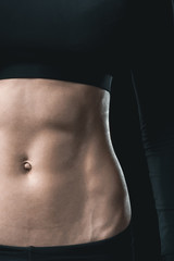 woman's muscular body with abs isolated on black. sport concept