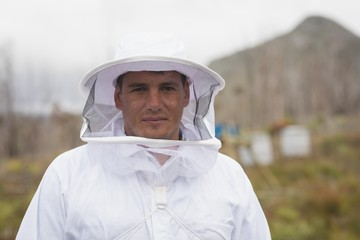 Portrait of man wearing bee suit at apiary