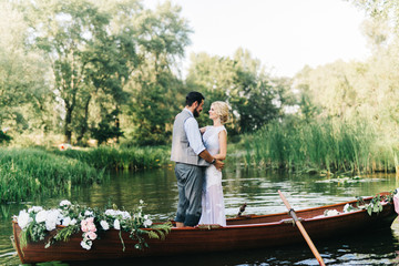 Young wedding couple posing on the boat
