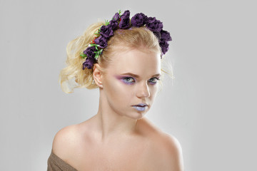 Fashion beauty model girl with flowers in her hair. Perfect creative make up and floral art hairstyle.