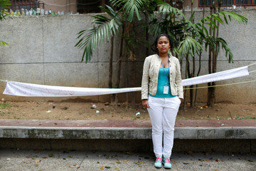 Wendy Ahumedo (23) poses for a picture while she waits for legal advice at the Labor Ministry after having been fired from a Medical service company, in Caracas