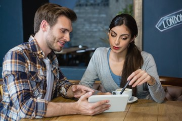Young couple using digital tablet while having coffee