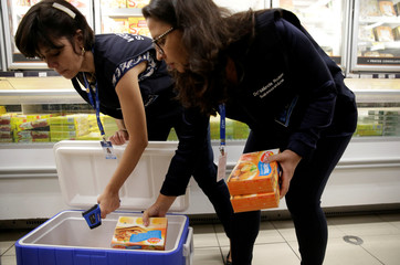 Members of the Public Health Surveillance Agency collect boxes of chicken nuggets to analyse in their laboratory, at a supermarket in Rio de Janeiro