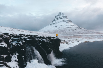 Person in yellow jacket standing in front of a mountain landscape with waterfalls in winter