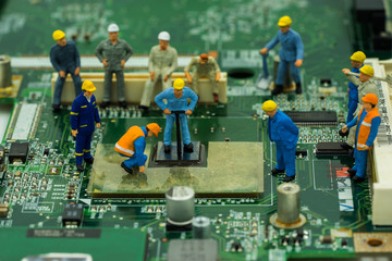 abstract mini worker team try to repair cpu on mainboard - can use to display or montage on product