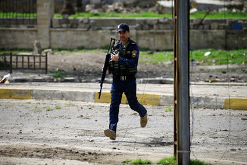 An officer of the federal police carries his weapons as he attempt to break into the Old City during a battle against Islamic State militants in Mosul