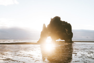 Beach rock formation at sunrise with tiny person