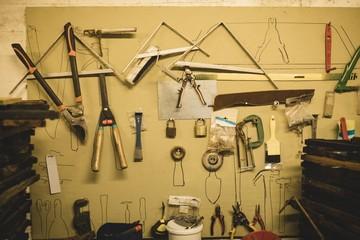 Tools hanging on wall at beekeeping factory