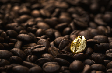 Individuality concept, close up of a single bright, gold coffee bean over many dark ones with copy space
